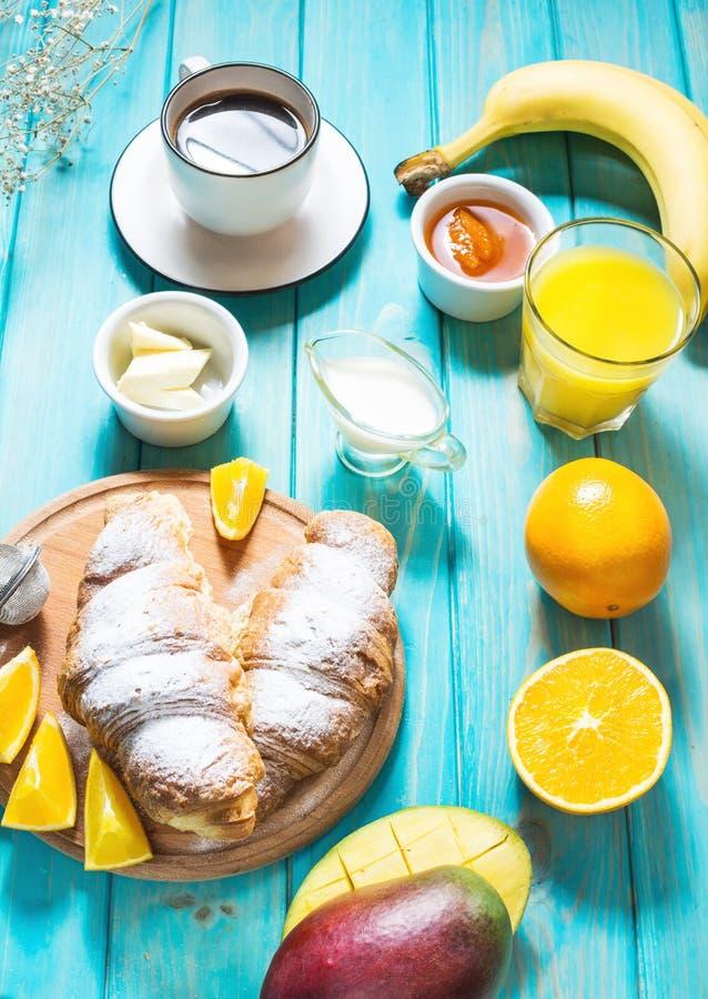 Het ontbijt diende met koffie, jus d'orange, croissants en vruchten op blauwe achtergrond royalty-vrije stock fotografie