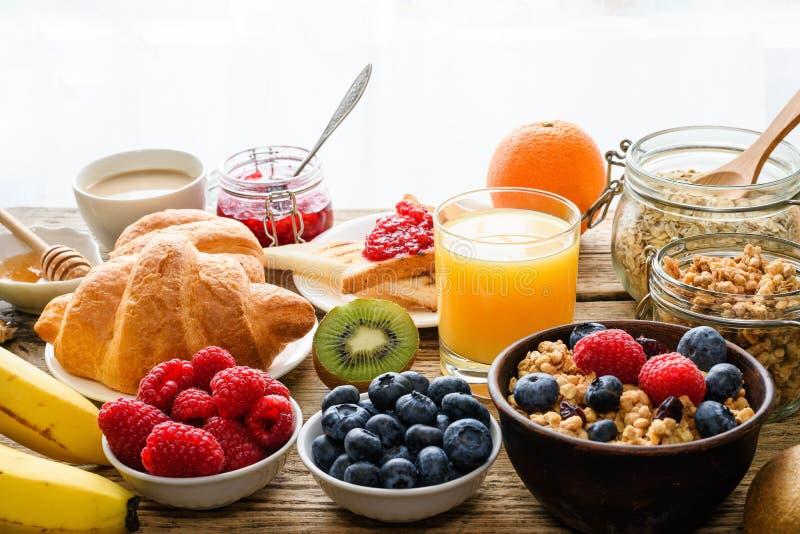Het ontbijt diende met koffie, jus d'orange, toosts, croissants, graangewassen, melk, noten en vruchten royalty-vrije stock foto's