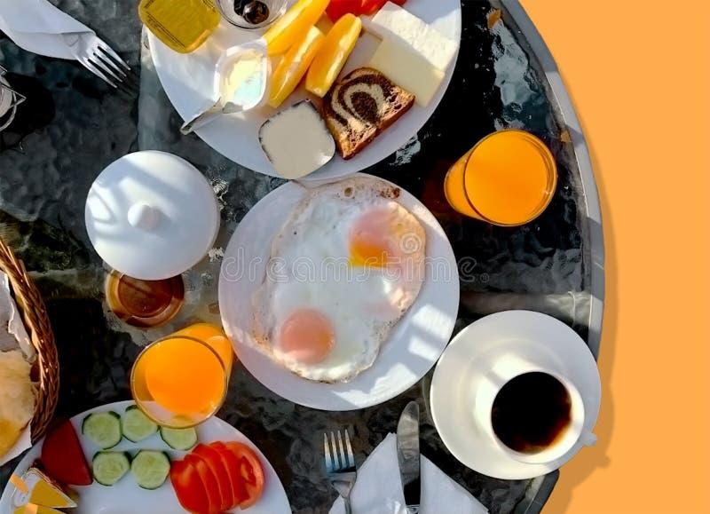 Het ontbijt diende met oranje stukken, brood, jam, boter, tomaten en komkommerplak en braadde ei royalty-vrije stock afbeeldingen