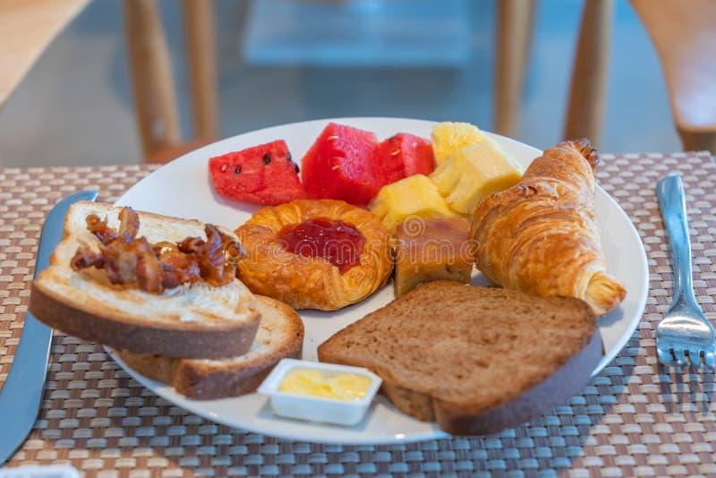 Het ontbijt met broodplakken, de vruchten, het croissant, de boter en de aardbei blokkeren stock fotografie