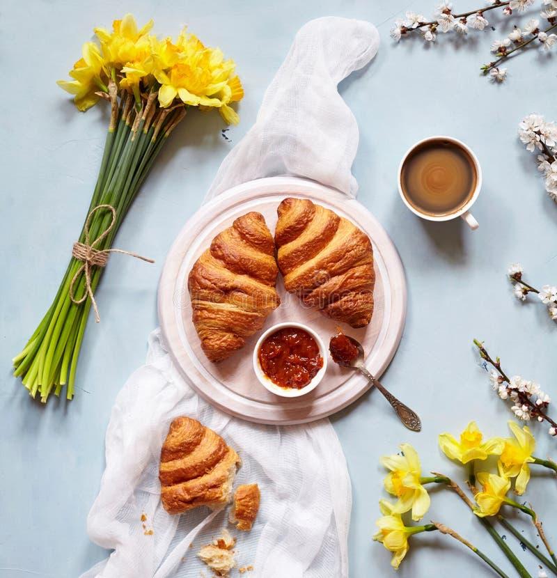 Het ontbijt met verse Franse croissants, jam en koffie met de lente bloeit boeket van gele narcissen op lichtblauw stock foto
