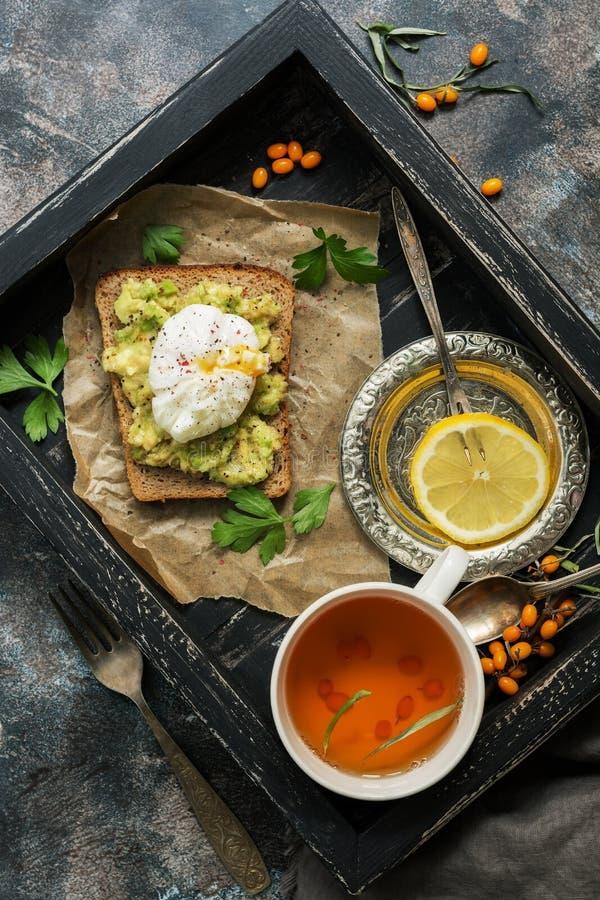 Het ontbijt stroopte ei, avocado guacamole sandwich, thee, citroen op een houten dienblad Rustieke achtergrond Thee met duindoorn stock afbeeldingen