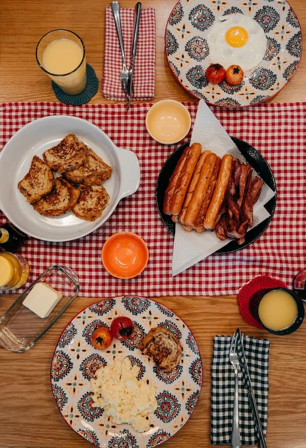 Het ontbijt van de huisstijl met knapperig bacon, eieren, Franse toost, worst en jus d'orange stock fotografie