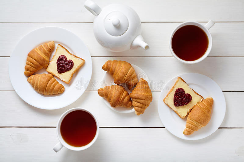 Het ontbijt voor paar met toosts, hart vormde jam, croissants, en thee op witte houten lijstachtergrond stock foto