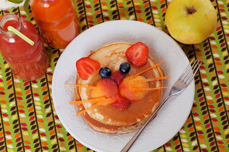 Het ontbijtpannekoeken die van kinderen gezicht van de kat, het katje, de aardbeibosbes en de abrikoos, leuk voedsel, honing glim stock fotografie