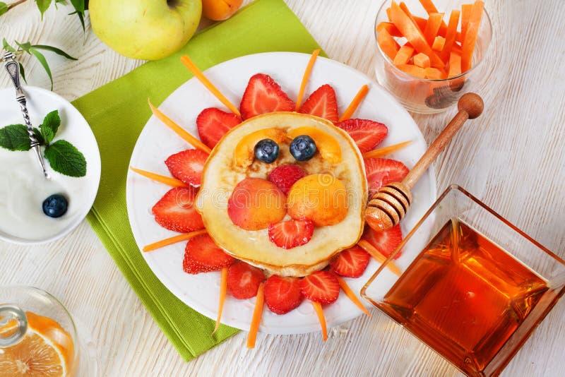 Het ontbijtpannekoeken die van kinderen gezicht van glimlachen stock afbeelding