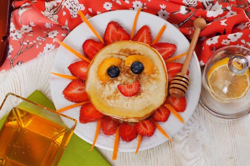 Het ontbijtpannekoeken die van kinderen gezicht van glimlachen royalty-vrije stock foto's