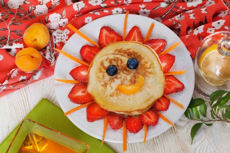 Het ontbijtpannekoeken die van kinderen gezicht van glimlachen stock afbeeldingen
