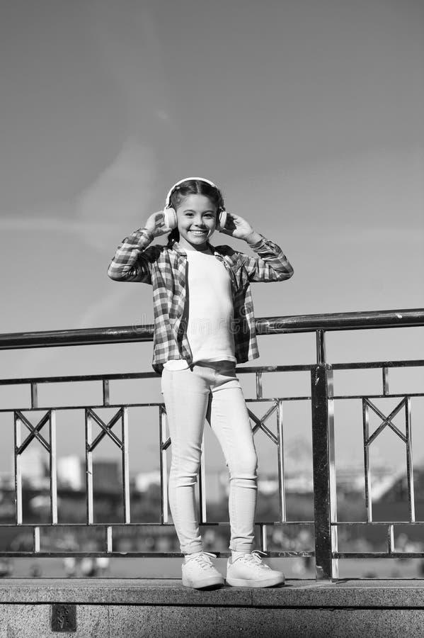 Het ontdekken van nieuwe muziekstijlen is grote manier in cultuur Het meisjeskind luistert muziek in openlucht met moderne hoofdt royalty-vrije stock fotografie