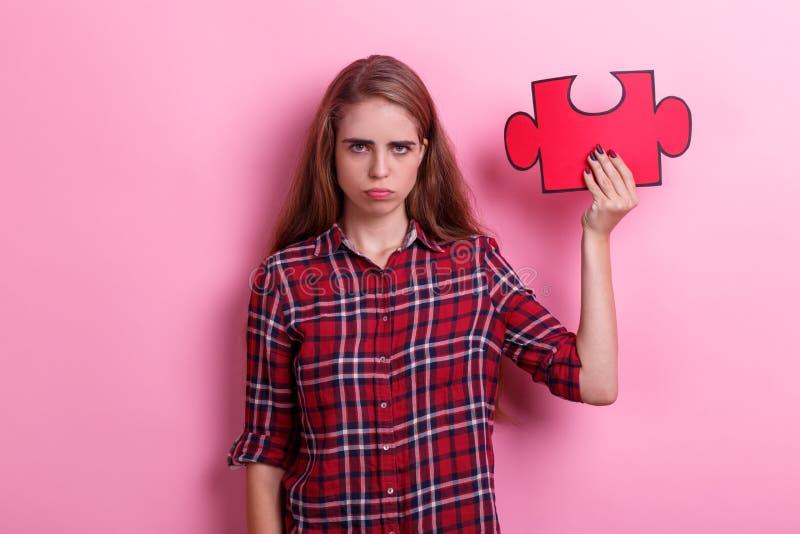 Het ontevreden meisje, houdt een rood raadsel op haar opgeheven hand Op een roze achtergrond stock afbeelding
