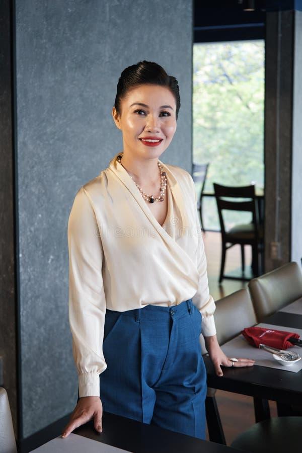 Het ontspannen Aziatische onderneemster glimlachen die zich in koffie bevinden stock foto