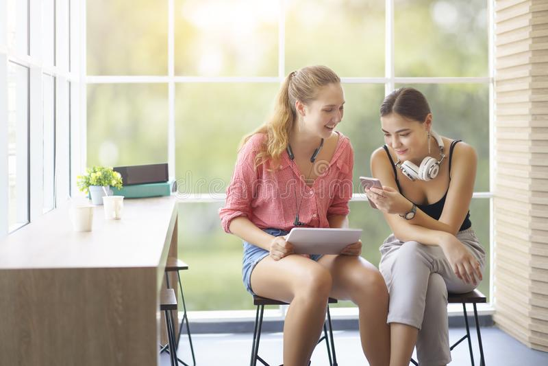 Het ontspannen beste vrienden jonge vrouwen gelukkig spreken, hebbend gesprek van levensstijlen, die technologie online smartphon stock foto