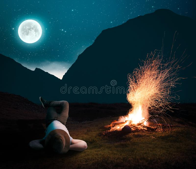 Het ontspannen in de nacht aan het brandkamp stock afbeeldingen