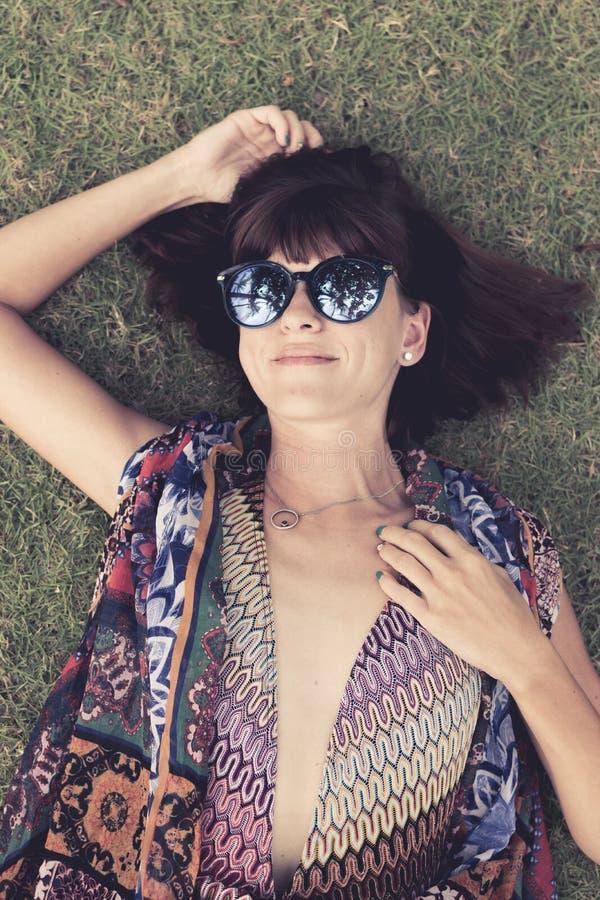 Het ontspannen in gras Hoogste mening die van mooie jonge vrouw in zonnebril en pareo op het groene gras in het park liggen van stock foto