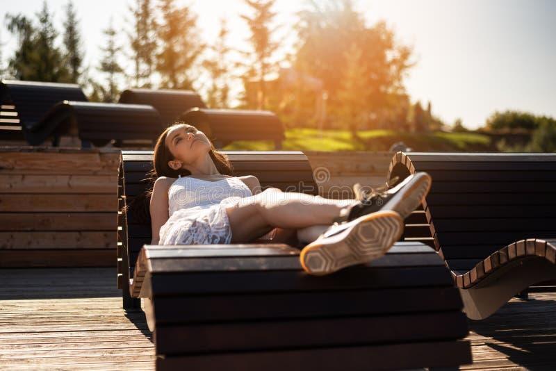 Het ontspannen jonge meisje liggen sunbed en het slapen in de zon royalty-vrije stock afbeeldingen