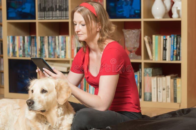 Het ontspannen met een hond en het bekijken de tablet stock afbeeldingen
