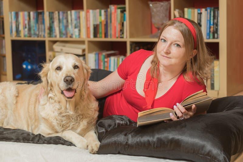 Het ontspannen met een hond en een boek die de camera bekijken royalty-vrije stock afbeelding
