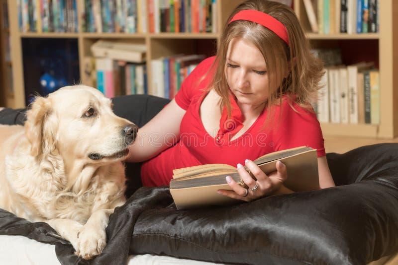 Het ontspannen met een hond en het lezen van een boek stock afbeelding