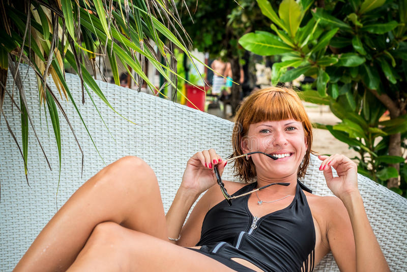 Het ontspannen op de ligstoel Mooie jonge vrouwen die in zonnebril op de ligstoel op het strand ontspannen Sexy vrouw royalty-vrije stock foto