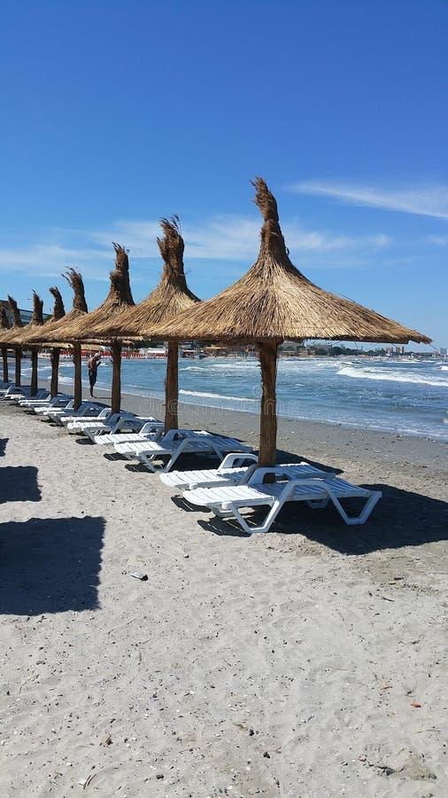 Het ontspannen op de strandparaplu's stock afbeeldingen