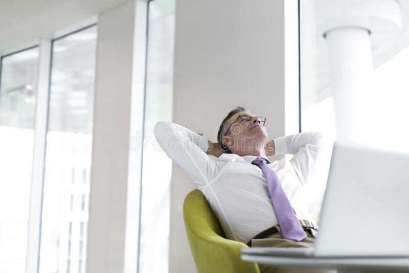 Het ontspannen rijpe zakenman doen leunen bij hal stock afbeelding
