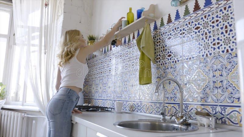 Het ontspannen sexy blonde stellen op keuken in ochtend actie Sexy jonge blondevrouw in de keuken thuis stock afbeelding