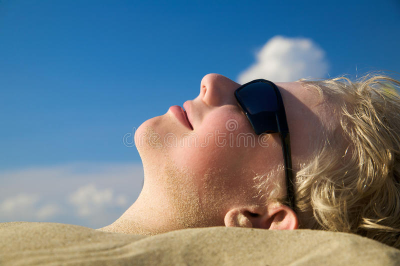 Het ontspannen van de jongen op de zomerstrand in zonnebril stock afbeelding