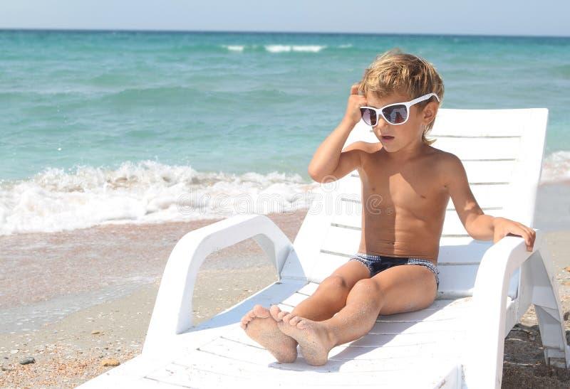 Het ontspannen van de jongen op strand stock afbeeldingen