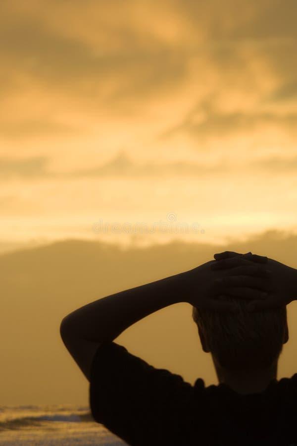 Het ontspannen van de jongen op strand bij zonsondergang stock afbeeldingen