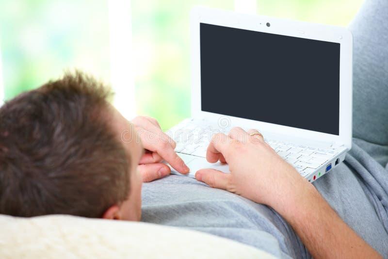 Het ontspannen van de mens met laptop stock fotografie