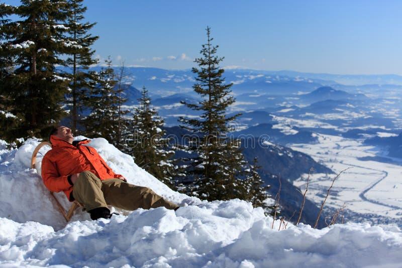 Het ontspannen van de mens in sneeuw stock foto