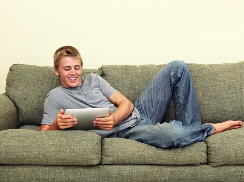 Het ontspannen van de tiener met tablet stock foto's