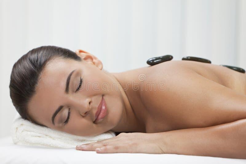 Het Ontspannen van de vrouw bij Kuuroord dat de Hete Massage van de Steen heeft royalty-vrije stock afbeeldingen