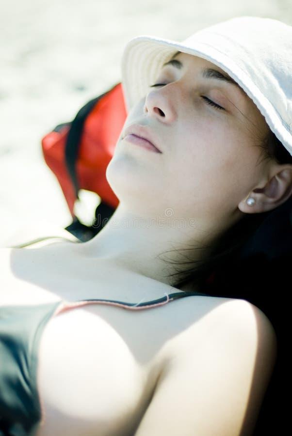 Het ontspannen van de vrouw in de zon royalty-vrije stock afbeelding