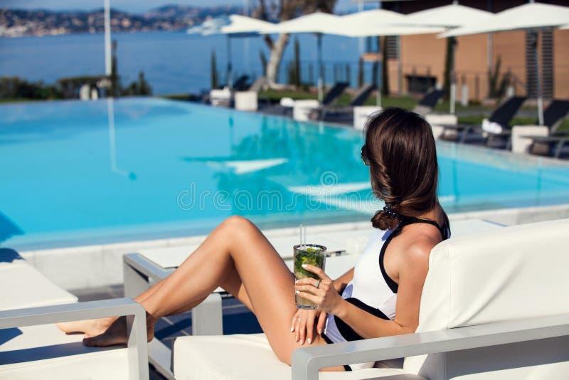 Het ontspannen van de vrouw door de pool royalty-vrije stock afbeeldingen