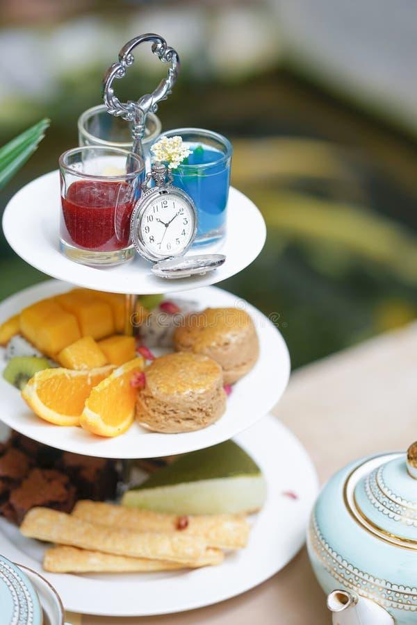 Het ontspannen van de vrouw drinkt thee Theetijd in de ochtend met verschillend soort dat wordt gediend stock fotografie