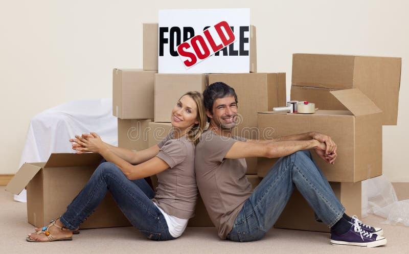 Het ontspannen van de vrouw en van de echtgenoot op vloer uitpakkende dozen stock fotografie