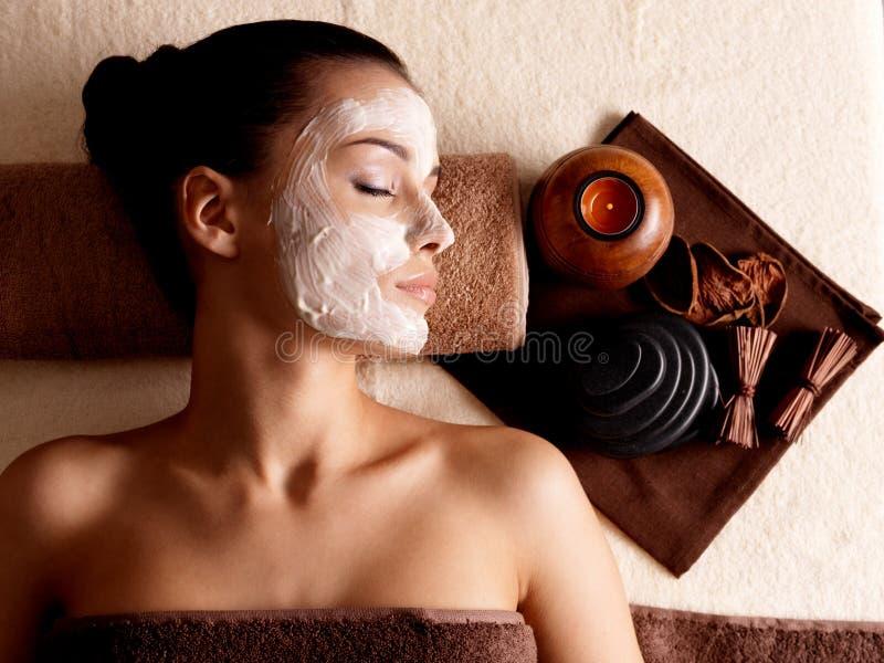 Het ontspannen van de vrouw met gezichtsmasker op gezicht bij schoonheidssalon royalty-vrije stock foto's