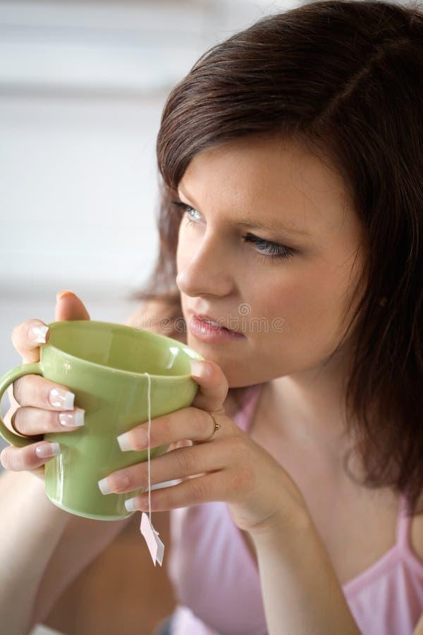 Het ontspannen van de vrouw met kop thee stock afbeeldingen