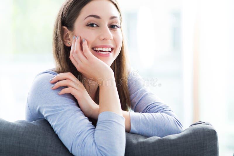 Het ontspannen van de vrouw op bank stock foto's