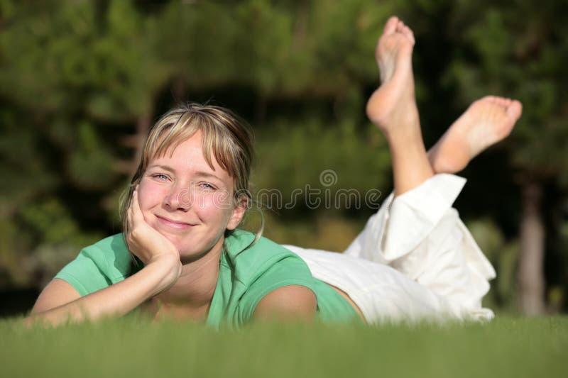 Het ontspannen van de vrouw op een gazon royalty-vrije stock fotografie