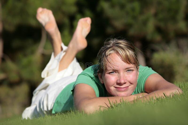 Het ontspannen van de vrouw op een gazon stock fotografie