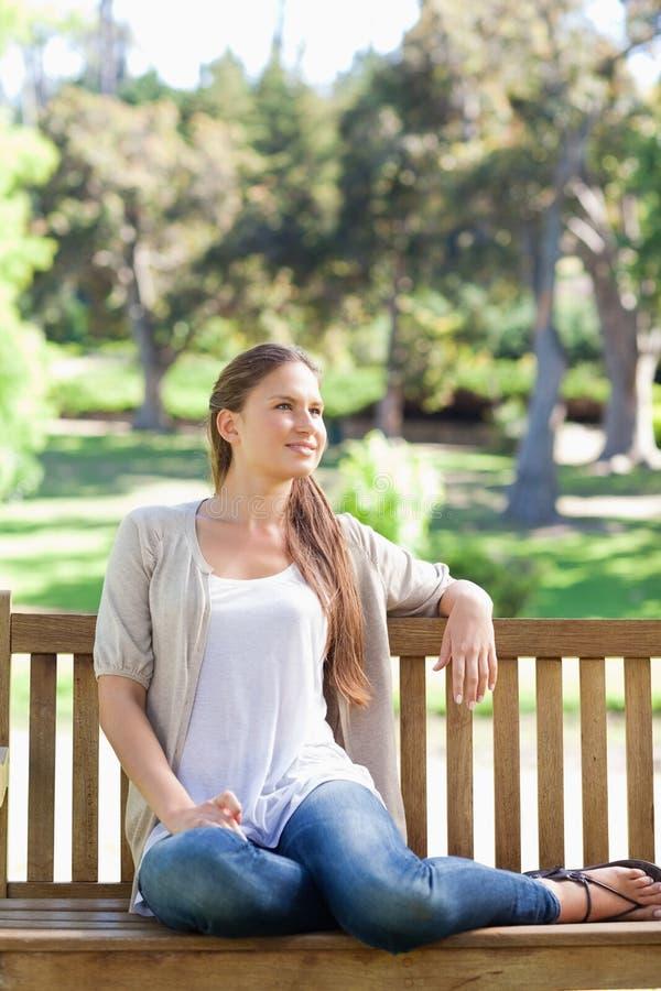 Het ontspannen van de vrouw op een parkbank stock afbeeldingen