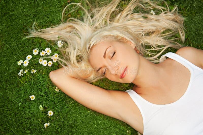 Het ontspannen van de vrouw op een weide stock foto's