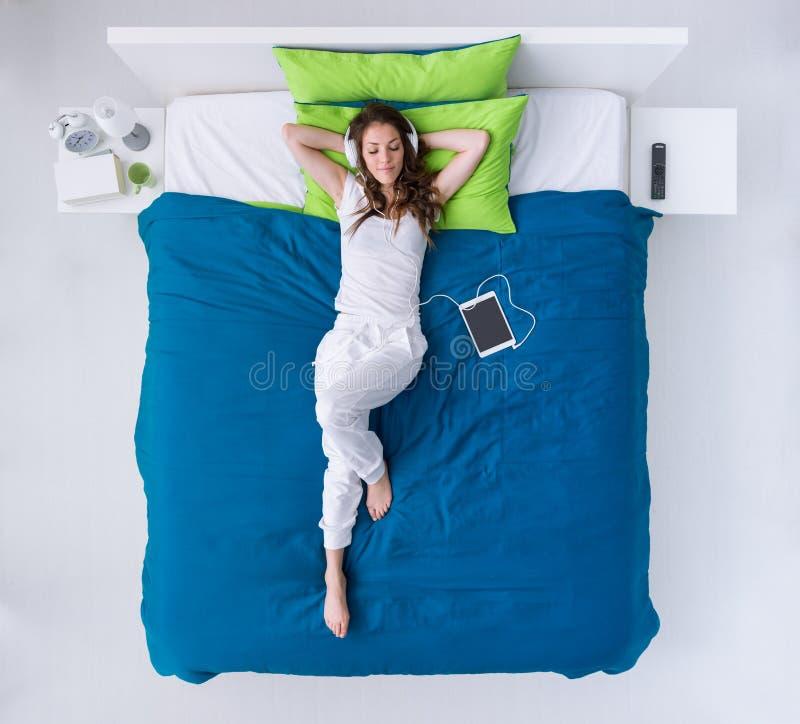 Het ontspannen van de vrouw op het bed royalty-vrije stock foto