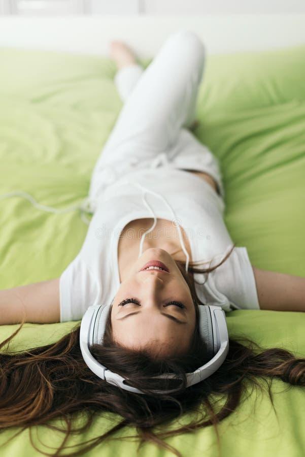 Het ontspannen van de vrouw op het bed stock foto