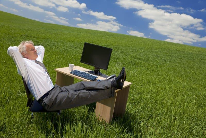 Het Ontspannen van de zakenman in een Groen Bureau stock foto's