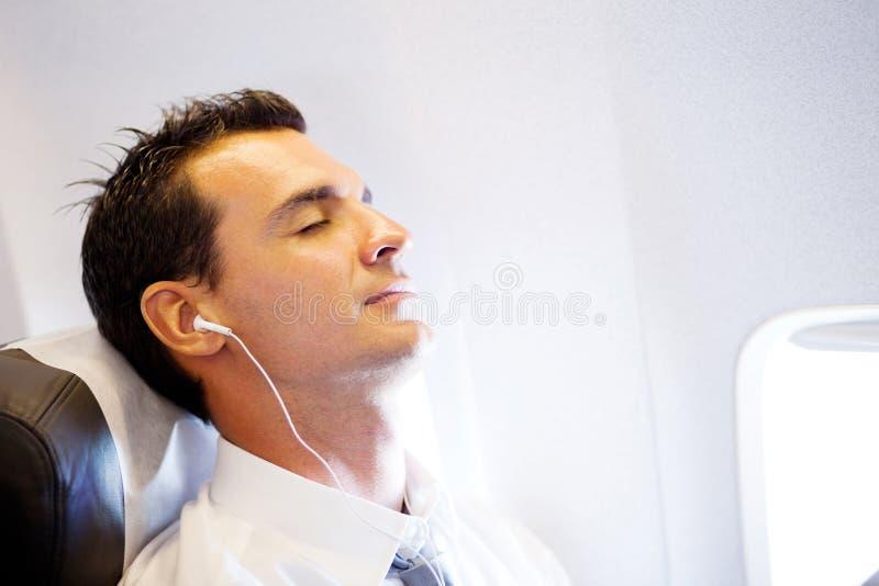 Het ontspannen van de zakenman op vliegtuig stock foto