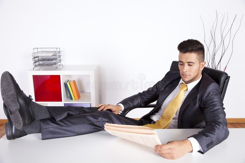 Het ontspannen van de zakenman op zijn kantoor stock foto's