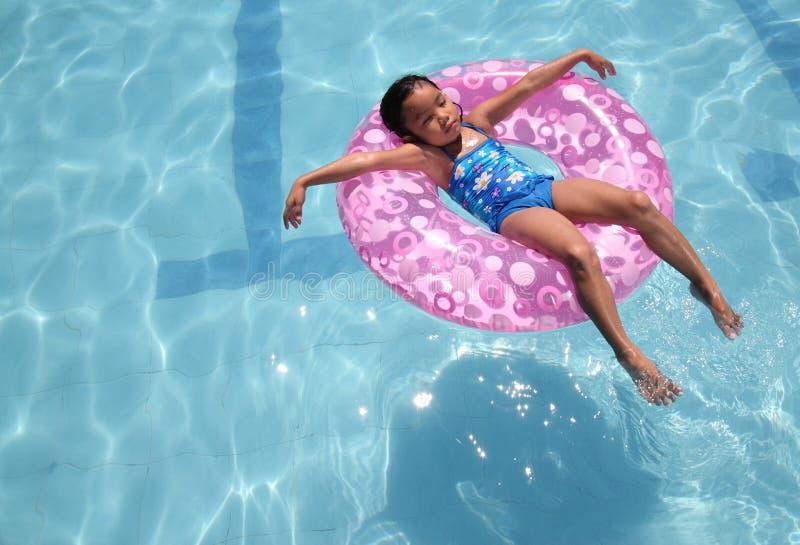 Het ontspannen van het kind bij de pool royalty-vrije stock afbeelding